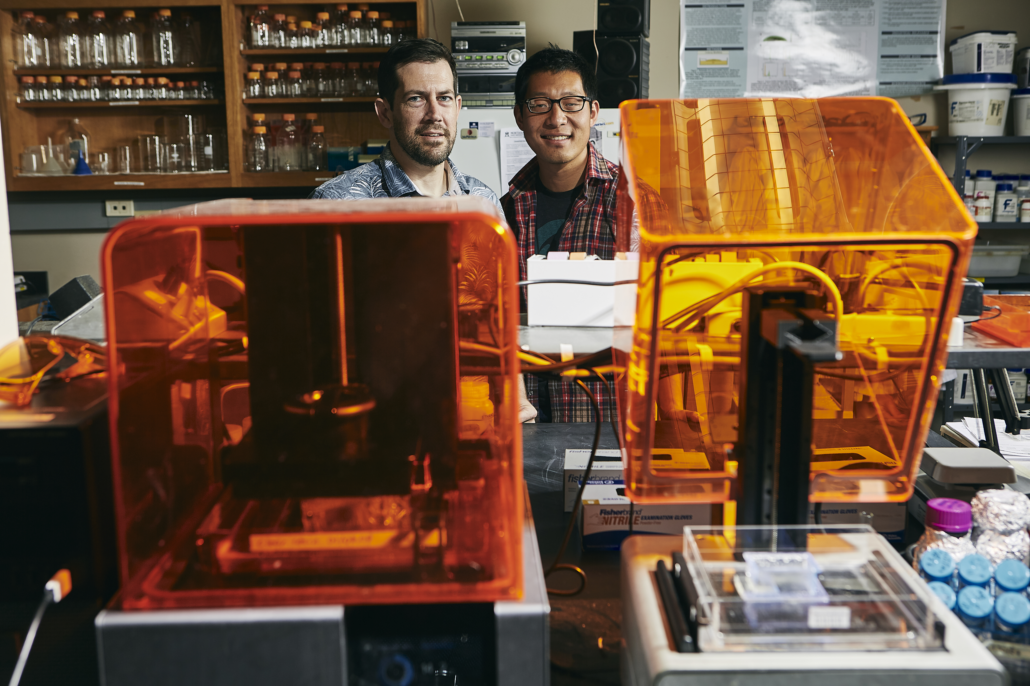James Wilking, left, and doctoral student Jason Zeng, shown with 3-D printers they will use to study how microbial communities interact in biofilms.